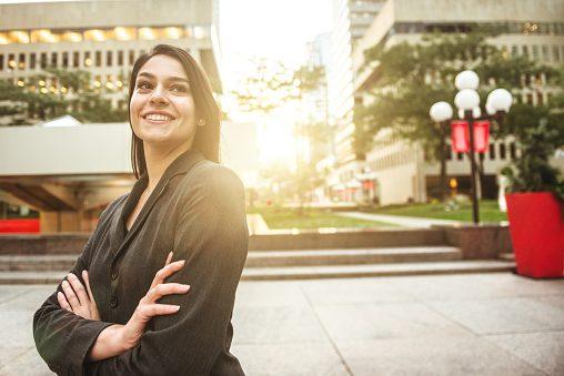 Female hard money broker with arm crossed on urban scene